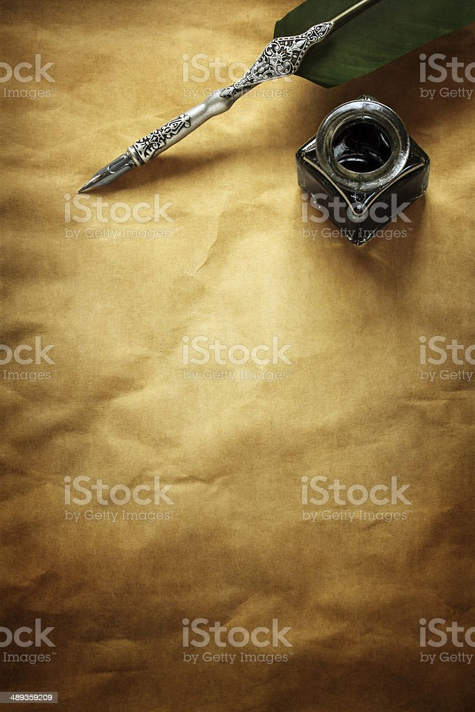 Quill pen and ink well on parchment paper stock photo