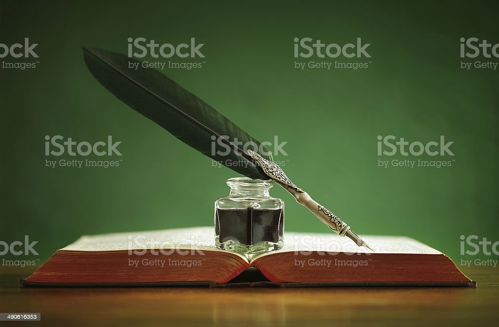Quill pen and inkwell on old book stock photo