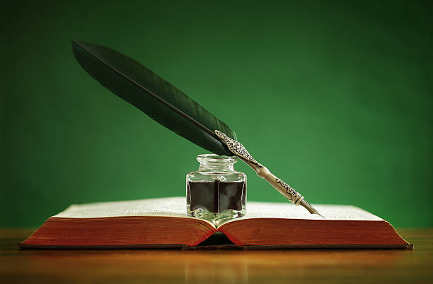 quill pen and inkwell on old book - ink well stock photos and pictures