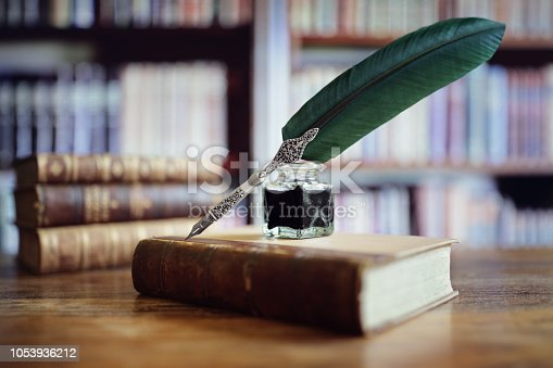 istock Quill pen on an old book in a library 1053936212
