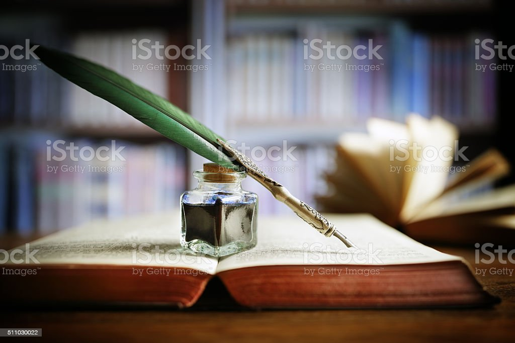 Quill pen on an old book in a library stock photo
