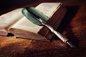 istock Quill pen on an old book 492598544