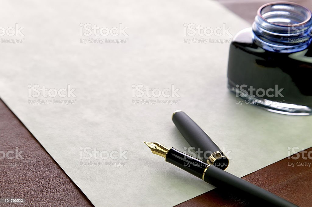 Quill pen with jar of ink next to old-fashioned paper royalty-free stock photo