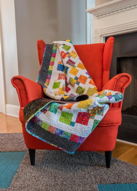 quilt drapiert über rückseite orange stuhl - patchwork decke stock-fotos und bilder