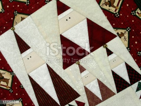 Detail of a seasonal quilted wallhanging featuring several triangularly shaped Santa Clauses; brass jingle bells decorate their hats.