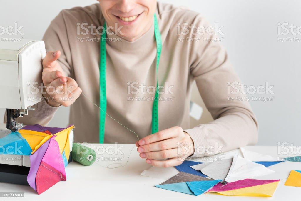 quilting and needlework - close-up on hands of a smiling male tailor, his fingers thread into the needle, hanging around his neck measuring tape, on table pieces stitched fabrics and spools of threads stock photo