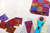 Quilting tools, sliced square bright pieces of batik, stack sewn blocks