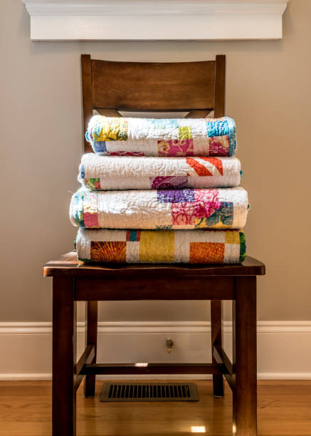 quilts stacked on wooden chair - quilt stock photos and pictures