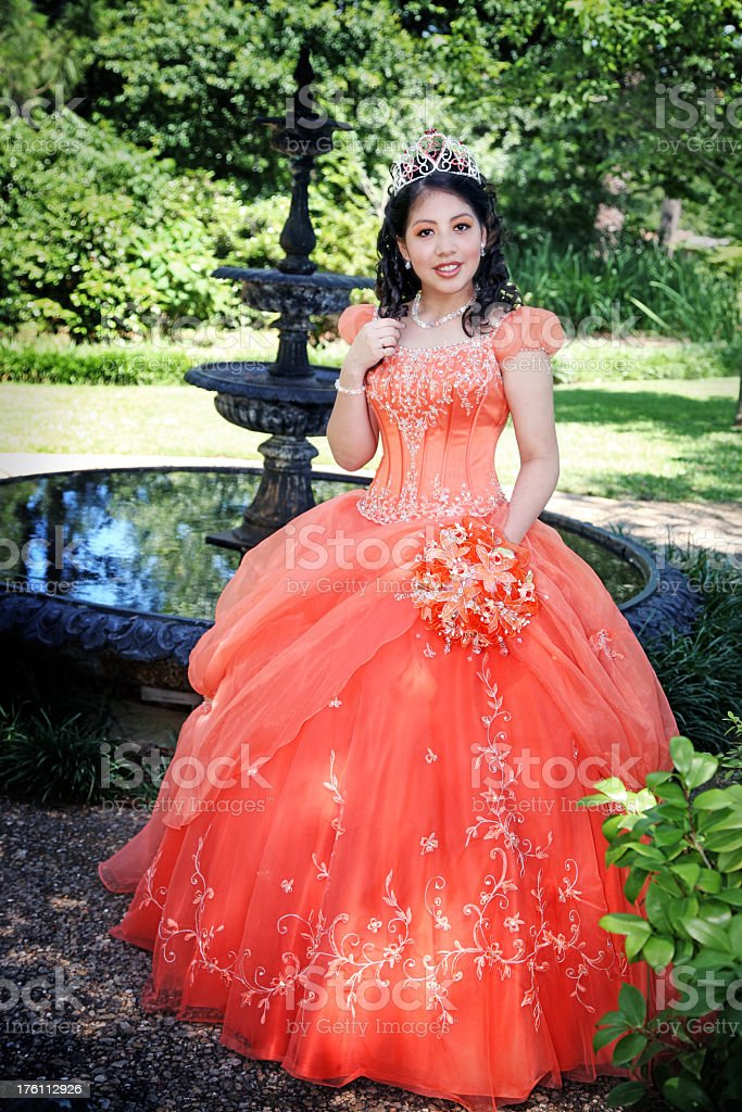 Quinceanera dressed up in beautiful ball gown, in a garden stock photo