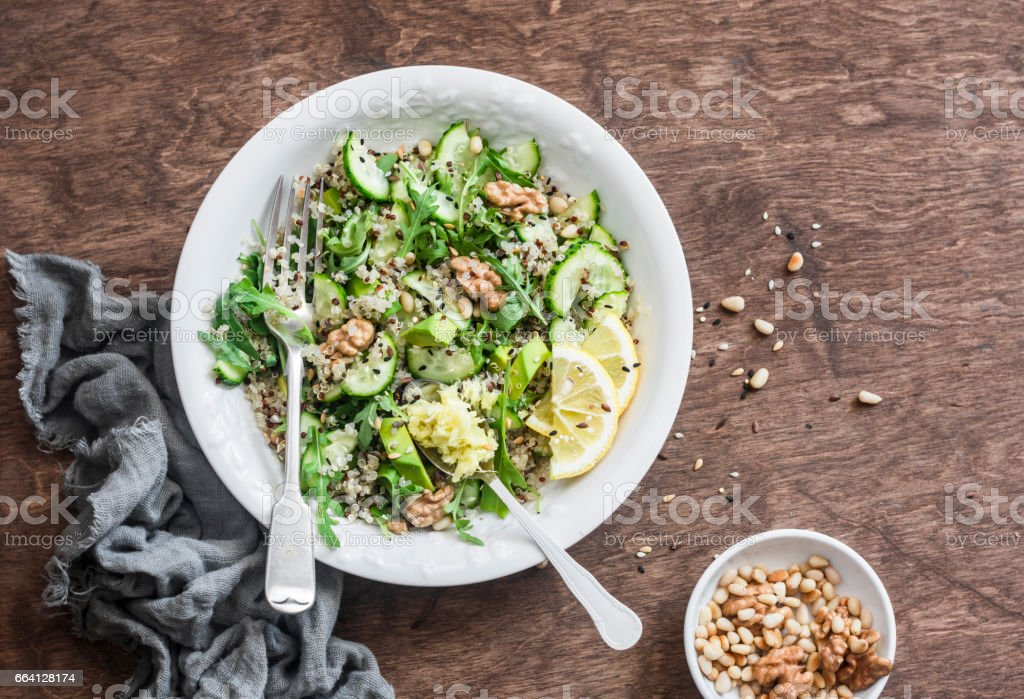 Quinoa and greens veggies salad for a spring detox. Salad with quinoa, cucumbers, avocado, arugula, ginger, flax seeds and nuts on wooden background, top view. Mediterranean style food concept stock photo