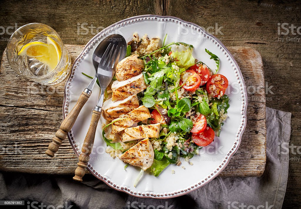 Quinoa and vegetable salad and grilled chicken stock photo
