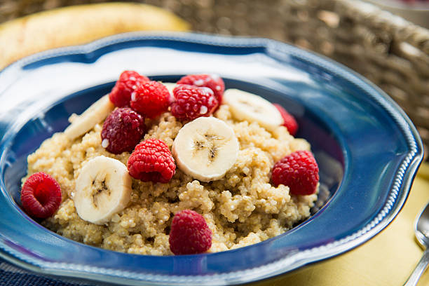 Quinoa Breakfast with Raspberries and Bananas A bowl of quinoa breakfast cereal with fresh raspberries and bananas. quinoa stock pictures, royalty-free photos & images