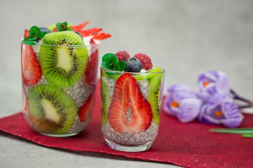 quinoa chia seeds dessert with almonds milk strawberry raspberry blueberry kiwi fresh mint napkin