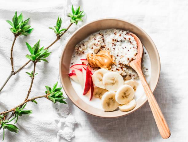 quinoa, kokosmilch, banane, apfel, erdnussbutter-brei auf hellem hintergrund, oben ansicht. köstliche ernährung, vegetarisches frühstück oder snack - getreidebrei stock-fotos und bilder