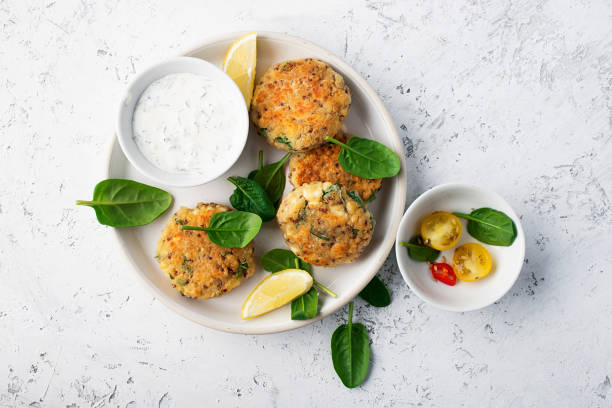 quinoa ricotta spinach fritters on a white dish with fresh spinach and hot chili peppers. top view - fritto foto e immagini stock