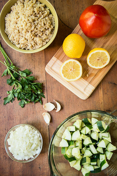 Quinoa Salad Ingredients From Above Ingredients for quinoa salad with cucumbers, tomatoes, onion, garlic and parsley from above. quinoa stock pictures, royalty-free photos & images