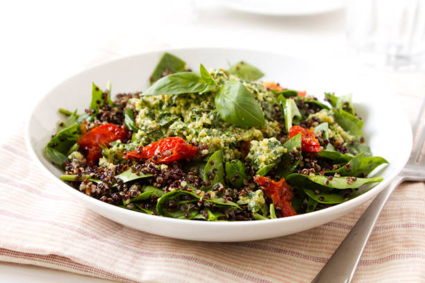Quinoa Salad A Quinoa Salad with sun-dried tomatoes and pesto vegetarian stock pictures, royalty-free photos & images