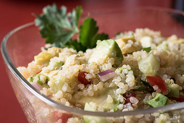 Quinoa Salad with Avocado, Cucumber and Tomato Cold quinoa salad with avocado, cucumber, tomato, red onion and parsley in a clear bowl. quinoa stock pictures, royalty-free photos & images