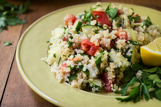 Quinoa Salad with Cucumbers and Tomatoes Horizontal Cold salad of quinoa, cucumber, tomato, onion and parsley sprinkled with fresh lemon juice. quinoa stock pictures, royalty-free photos & images