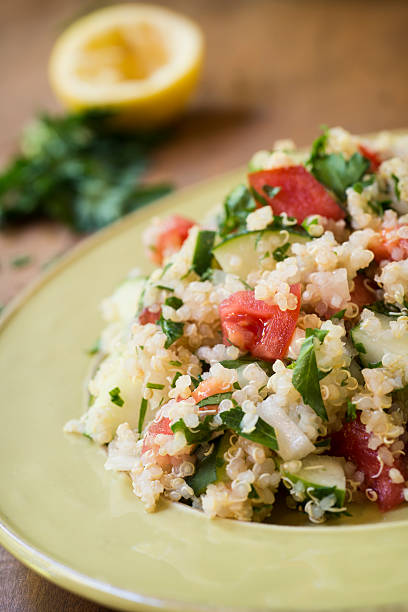 """Quinoa Salad with Cucumbers and Tomatoes Vertical Close-up """"A cold salad of quinoa, cucumbers, tomatoes, onions, and parsley topped with lemon juice.Similar Images:"""" quinoa stock pictures, royalty-free photos & images"""