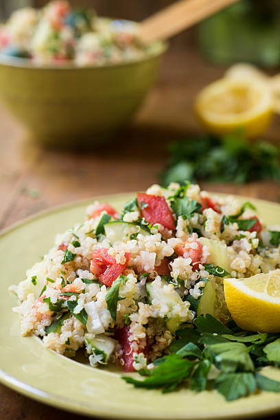 """Quinoa Salad with Cucumbers and Tomatoes Vertical """"A cold salad of quinoa, cucumbers, tomatoes, onions, and parsley topped with lemon juice.Similar Images:"""" quinoa stock pictures, royalty-free photos & images"""