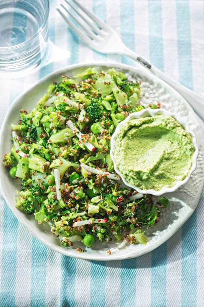 quinoa & supergreen salat. brokkoli, rettich, erbsen & quinoa mit hummus & spinat dip - radieschen salat stock-fotos und bilder