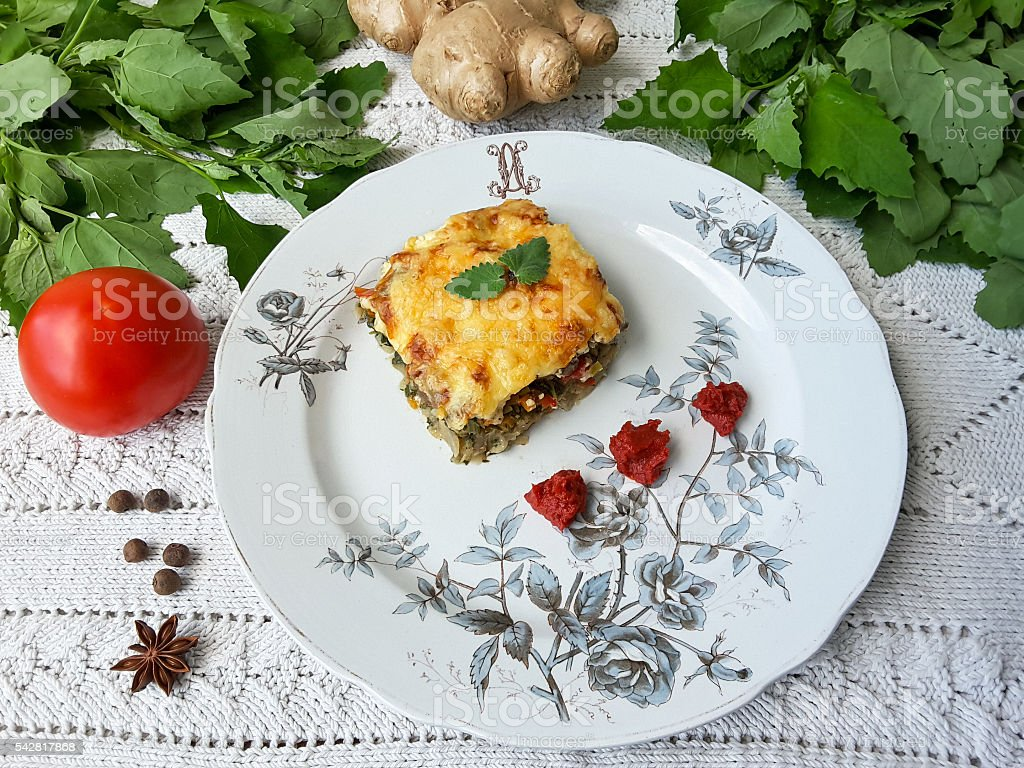 Quinoa tomato ginger gratin on plate, organic food with weed стоковое фото