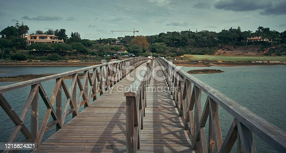 Quinta do Lago view in Algarve, Portugal. Wooden bridge along the river and blue sky with clouds