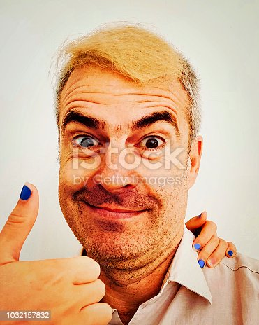 istock Quirky portrait of mature man with bad blonde hair toupe smiling 1032157832