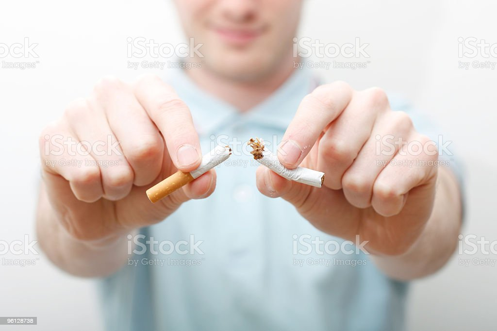 Quit smoking man breaking cigarette in half royalty-free stock photo