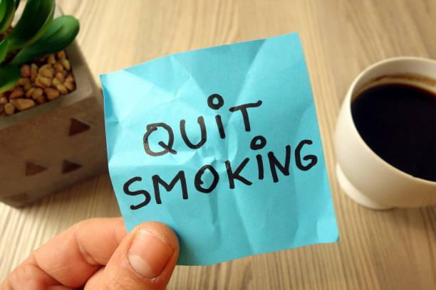 Quit smoking - motivational reminder handwritten on sticky note stock photo