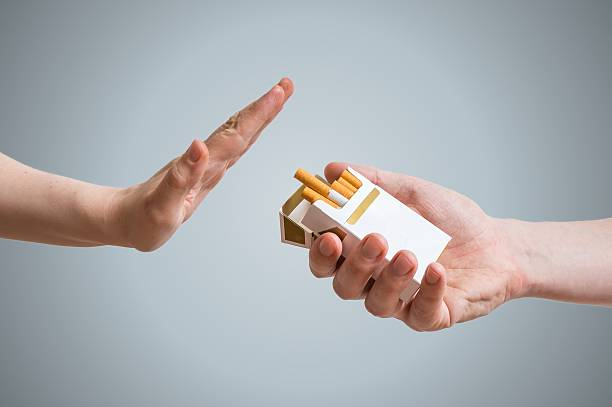 quitting smoking concept. hand is refusing cigarette offer. - sigaretta foto e immagini stock