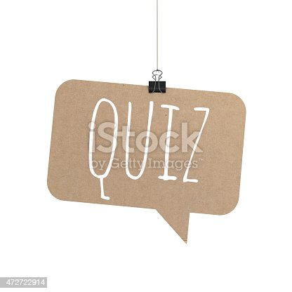 A  3D representation of a speech bubble hanging on a plain white background. The speech bubble is hanging from a binder paper clip that is attached to a piece of string. The bubble has a cardboard texture. The background is pure white. written on the speech bubble in white text is Quiz