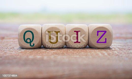 Quiz word written on cube shape wooden blocks on wooden table.