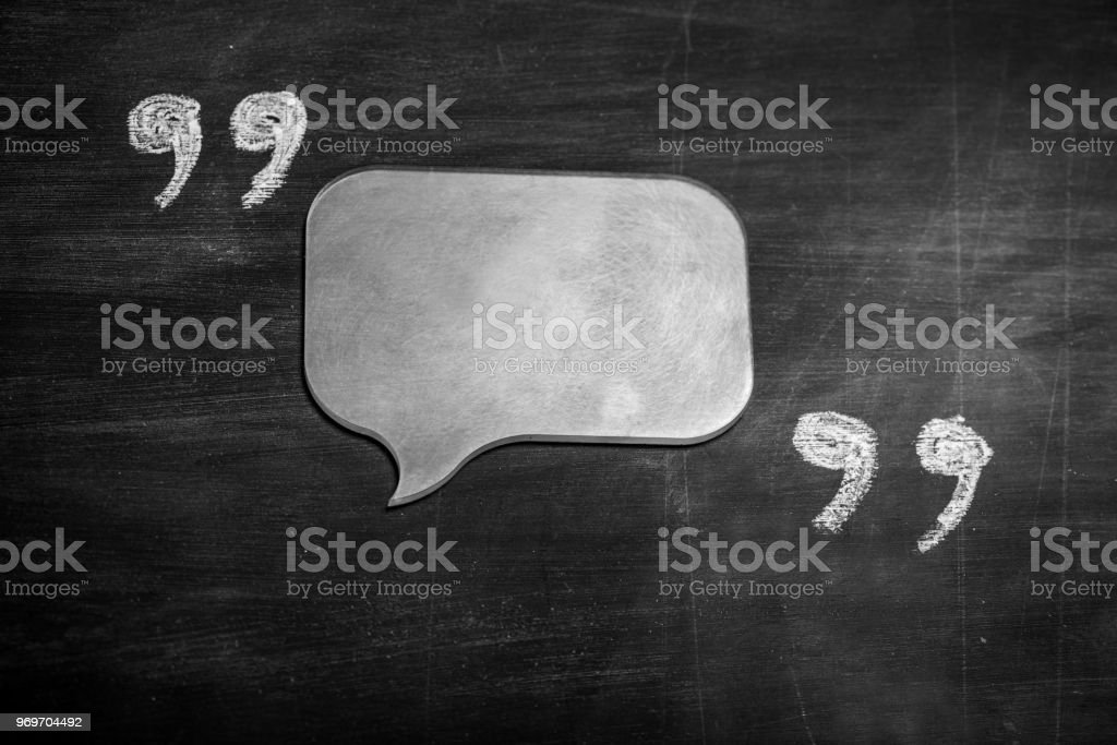Quotation marks and speach bubble on blackboard stock photo