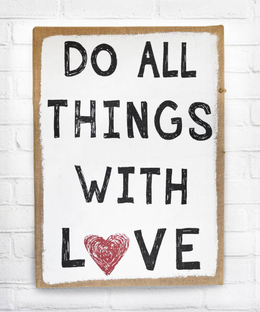 Quote do all things with love text on hanging sign board against white brick wall stock photo