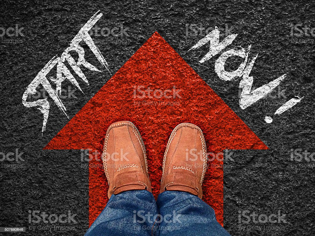 Quote:' Start now' on aerial view of shoe on road stock photo