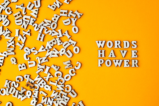 Quote WORDS HAVE POWER made out of wooden letters on bright yellow background. Motivational Words Quotes Concept