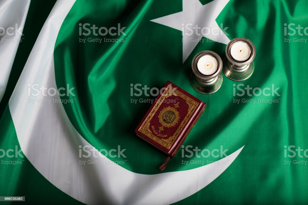 Quran and candles on a flag of Pakistan. Translation into English - the book contains verses of Koran. stock photo