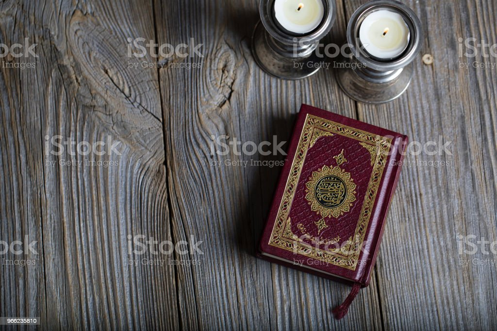 Quran and candles on a wooden surface. Translation into English - the book contains verses of Koran. stock photo