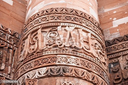 Close up view of the tower of Qutub Minar in Delhi, with architecture details.