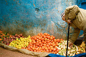 Rabat, Morocco: A stooped senior man with a cane and skullcap shops for produce in the Rabat Medina.