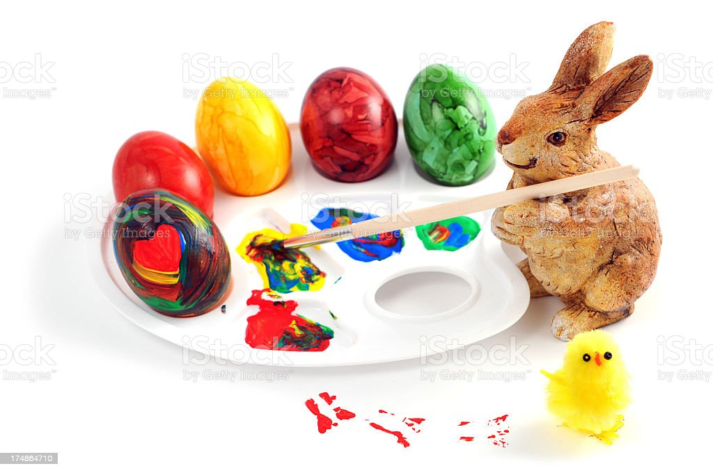 rabbit decorating easter eggs with painbrush and colours royalty-free stock photo