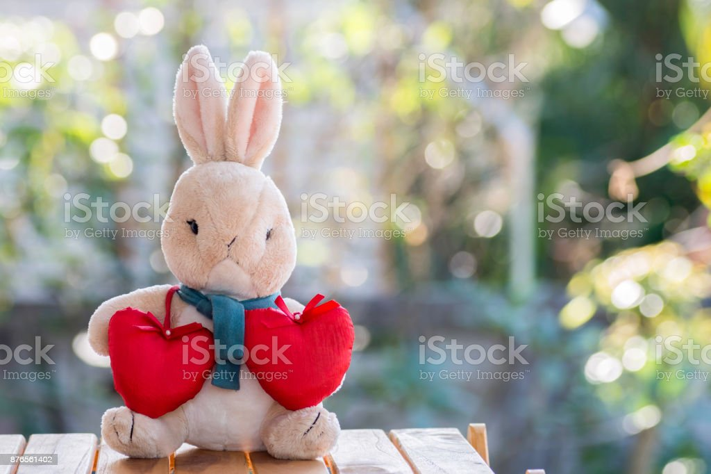 rabbit doll with red heart on the wooden floor stock photo