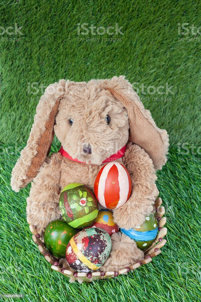 Rabbit, sit and holding colorful eggs in basket on grass stock photo