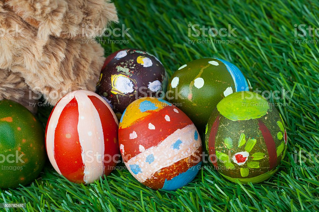 Rabbit, sit on green grass and group of colorful eggs stock photo