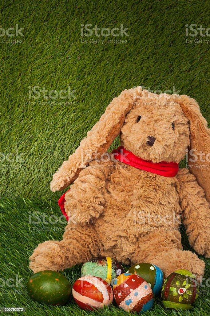 Rabbit, sit on green grass with group of colorful eggs stock photo