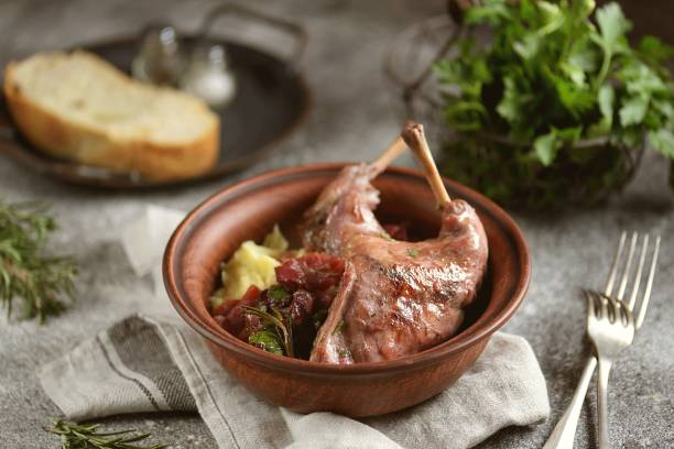 Rabbit stewed in wine with vegetables, rosemary and cherry. stock photo