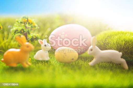 Rabbit toys with easter eggs on a meadow grass.