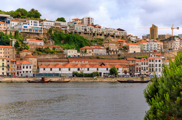 Rabelo boats with barrels of port docked on the Douro in front of the famous Portuguese wine cellars in Porto, Portugal stock photo
